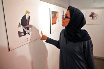 "An Iranian woman looks at a cartoon depicting U.S. President Donald Trump in an exhibition in Tehran, Iran, Monday, July 3, 2017. Iranians have organized a ""Trumpism"" cartoon contest in which hundreds of participants have been invited to submit artwork mocking the U.S. leader. (AP Photo/Vahid Salemi)"